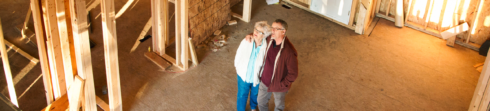 Senior couple standing in the construction zone of their dream home.