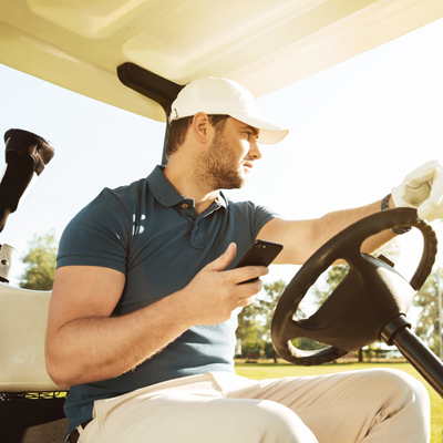 photo of man on a golf cart checking his mobile phone