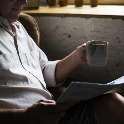 photo of a man reading paper and holding a mug