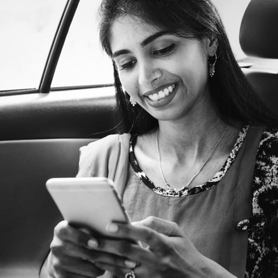 photo of a woman looking at her mobile in a car
